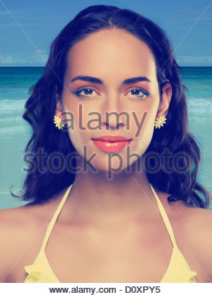 Young woman wearing yellow bikini and earrings - Stock Image