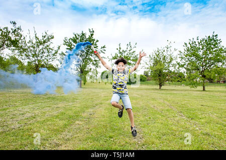 Happy carefree young boy playing with a blue flare running across the grass trailing smoke behind him a fresh green park or garden - Stock Image