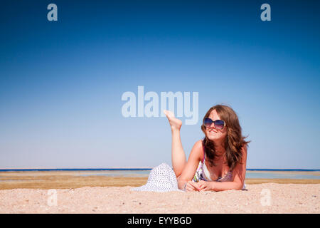 The young beautiful girl in a sunglasses on vacation, on a sunny beach - Stock Image