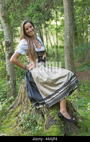 Woman With A Black Dirndl With Gold-Colored Skirt In Sitting On A Mighty Tree Stump - Stock Image
