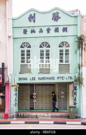 Singapore - 21st December 2018: A man consults his mobile phone as he walks past a shophouse. The city still has many such buildings. - Stock Image
