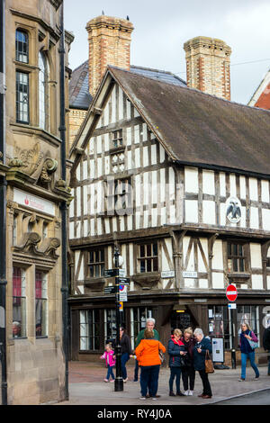 people shoppers shopping on the high Street in the Shropshire market town of Oswestry with a view of the black and white half timbered Llwyd Mansion. - Stock Image