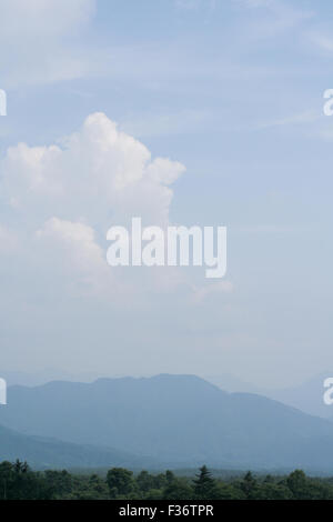 clouds blue sky green trees haze - Stock Image