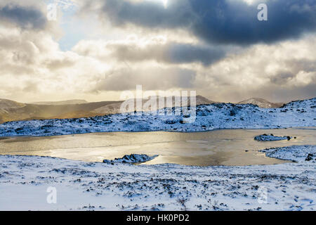 Winter snow scene by Llyn y Foel lake on slopes of Moel Siabod in Snowdonia National Park. Capel Curig, Conwy, Wales, - Stock Image