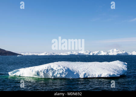 Icebergs floating out into cold Arctic ocean sea from Ilulissat Icefjord fed by most productive glacier in northern - Stock Image