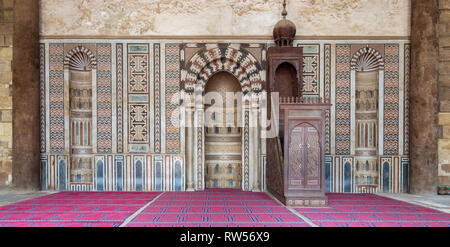 Colorful decorated marble wall with engraved Mihrab (niche) and wooden Minbar (Platform) at the public historical Mosque of Al Nasir Mohammad Ibn Qala - Stock Image
