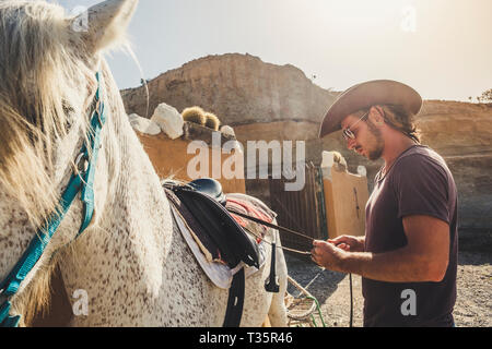 Young cute caucasian man in farm life cowboy style prepare her best friend white horse to go riding together enjoying the outdoor leisure activity and - Stock Image