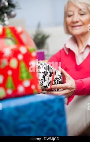 Senior Woman Holding Christmas Present - Stock Image
