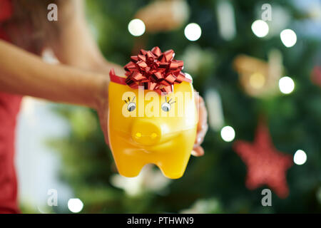 Closeup on yellow piggy bank with red bow in a hand of woman near Christmas tree - Stock Image
