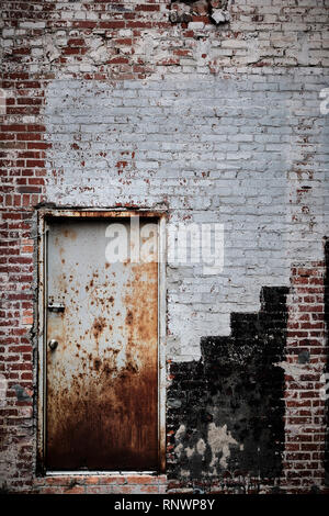 Old rusty metal or steel door in a weathered brick wall suitable for a rustic background. - Stock Image