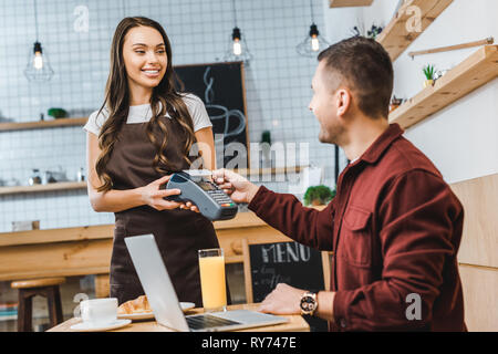 beautiful waitress holding terminal wile freelancer sitting at table with laptop and paying with smartphone in coffee house - Stock Image