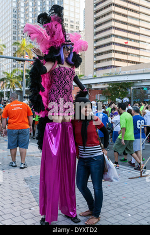 Female stilt walker in colorful costume with young woman spectator at 2014 Mercedes-Benz Corporate Run in Miami, Florida, USA. - Stock Image