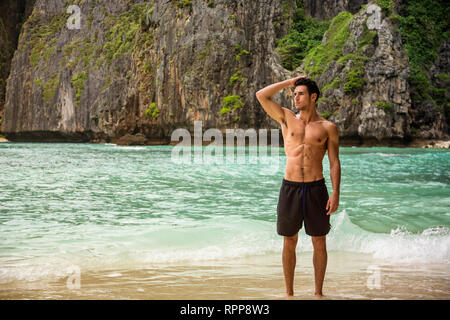 Young man standing on edge of the ocean - Stock Image