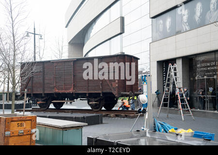 """New York, USA. 31st Mar, 2019. A German National Railroad freight car was installed on the plaza in front of the Museum of Jewish Heritage in Battery Park City, Manhattan, New York, as part of the museum's upcoming exhibition, """"Auschwitz. Not long ago. Not far away."""" This freight car, which would have been packed with 80 to 100 people, was one of many that the Nazis employed to transport people — most of them, Jews — to Auschwitz to be killed. Credit: Terese Loeb Kreuzer/Alamy Live News - Stock Image"""