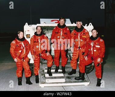 (17 Nov 1988) --- STS-27 Atlantis, Orbiter Vehicle (OV) 104, crewmembers participate in the terminal countdown demonstration test (TCDT) at the Kennedy Space Center (KSC). Standing in front of the M113 tracked rescue vehicle (armored personnel carrier (APC)) are left to right Mission Specialist (MS) William M. Shepherd, Pilot Guy S. Gardner, Commander Robert L. Gibson, MS Richard M. Mullane, and MS Jerry L. Ross. Crewmembers are wearing orange partial pressure or launch and entry suits (LES). - Stock Image