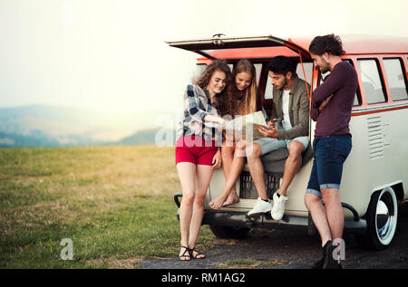 A group of young friends on a roadtrip through countryside, looking at map. - Stock Image