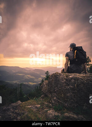 Man silhouette stay on sharp rock peak. Satisfy hiker enjoy view. Tall man on rocky cliff watching down to landscape during sunset - Stock Image