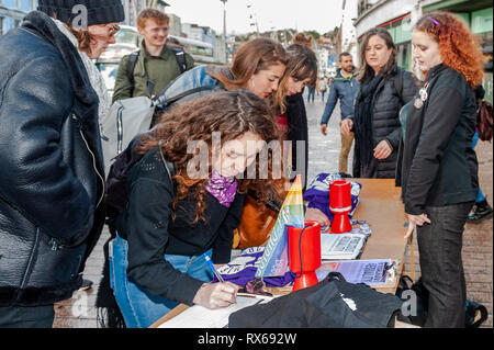 Cork, Ireland. 8th March, 2019. Women sign a petition for change at a '#Walkout 4 Equality' on International Women's Day on Patrick Street, Cork. The women are protesting sexual violence, the 14%pay gap and the cervical check scandal, as well as other issues. Credit: Andy Gibson/Alamy Live News. - Stock Image