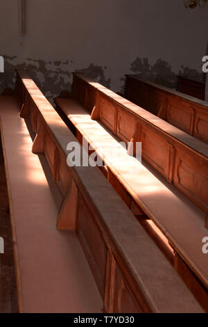 interior view of old church walls crumble and empty wooden pews without people, rows of wooden church benches lit by the sun through church windows - Stock Image