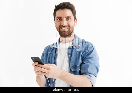 Portrait of a handsome bearded man wearing casual clothes standing isolated over white background, listening to music with earphones, holding mobile p - Stock Image