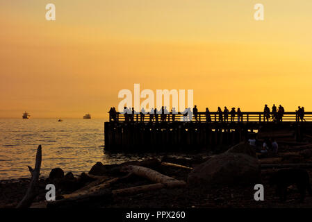 Silhouettes of people on the pier at sunset in Ambleside in West Vancouver, BC, Canada. - Stock Image