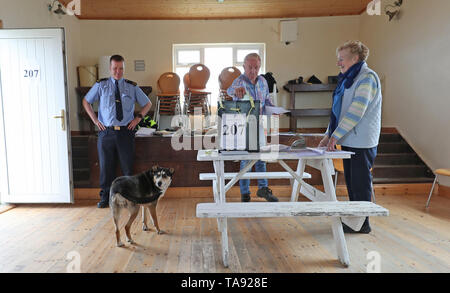 Presiding Officer Carmel McBride and Garda Adrian McGettigan watch a dog named Lucky as a voter casts his vote at the polling station on the island of Inishbofin. Voters on the remote isle off the coast of Donegal were among the first to cast their ballots in the local and European election, a day ahead of the rest of the country. - Stock Image