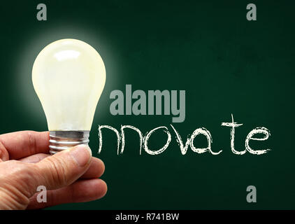 Man holding illuminated bulb with bare hands against chalkboard with the word Innovate. Concept of bright idea, innovation, imagination, inspiration,  - Stock Image