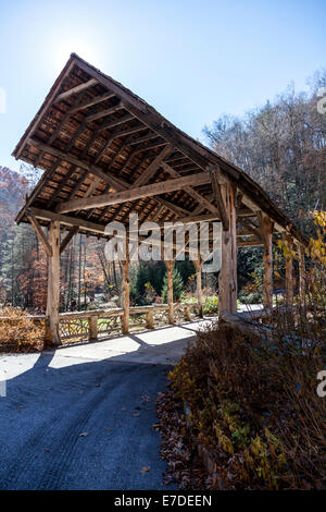 Rustic log and timber covered bridge leads to private development along west fork Tuckasegee River just south of - Stock Image