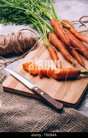 Still life with a carrot sliced on a cutting board with a fresh carrot on the table - Stock Image
