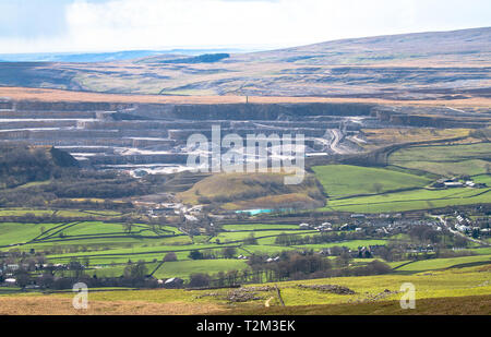 A massive rock quarry is seen from a distance in the Peak District, England. - Stock Image