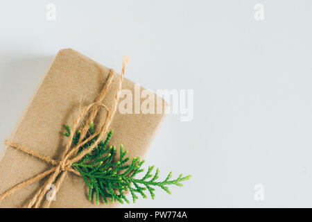 Small Gift Box Wrapped in Craft Paper with Juniper Twig on White Background. Christmas New Years Presents Shopping Sale. Copy Space. Poster Banner Cou - Stock Image
