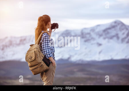 Beautiful woman with backpack is taking photo of mountain - Stock Image