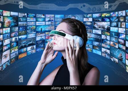 young woman wearing heads mount display and various pictures. internet streaming service concept. - Stock Image