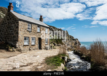A traditional stone built cottage on the coast, with a path past the front door. - Stock Image