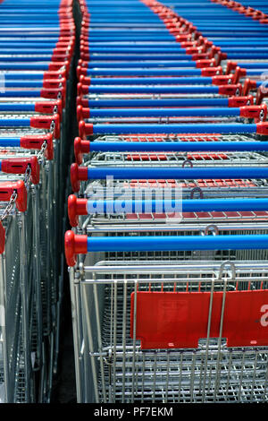 red and blue supermarket shopping trollie carts parked together outside store. Piacenza, Italy, Europe. - Stock Image