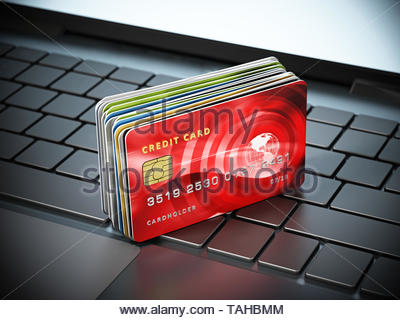 Credit cards standing on laptop computer keyboard. 3D illustration. - Stock Image