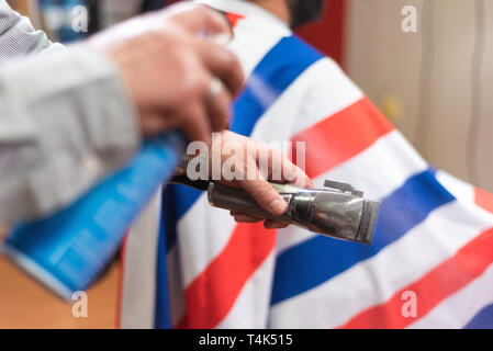 Barber cleaning electric hair clipper at barber shop. - Stock Image