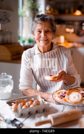 An elderly woman making cakes in a kitchen at home. - Stock Image