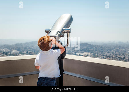 Young red haired boy looks through tourist binoculars at the sky in Los Angeles in California. - Stock Image