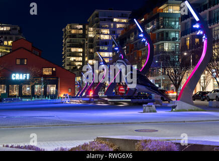 Olympic Village Square in Vancouver Canada at Night, with large bird sculpture and craft brewery. - Stock Image