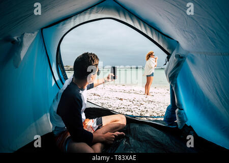 Alternative tent campiing vacation concept for travelers and wild lifestyle people with boy taking picture to woman at the beach enjoying the nature a - Stock Image