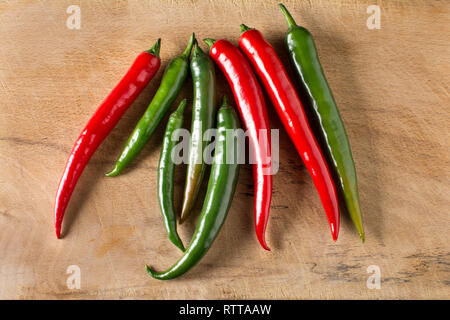 Red and green hot chilli peppers on a carving board with knife - Stock Image