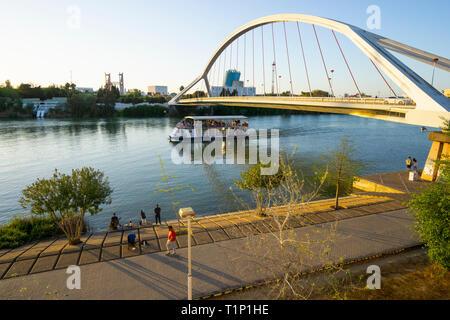 A tour boat passing under the Puente de la Barqueta on the Guadalquivir River in Seville - Stock Image