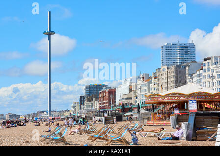 Beachgoers enjoy the sun in Brighton, with British Airways i360 viewing platform in the background. - Stock Image