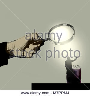 Hand holding magnifying glass over politician at podium - Stock Image