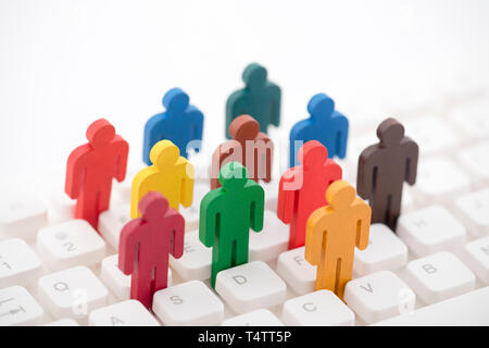 Colorful painted group of people figures on computer keyboard - Stock Image