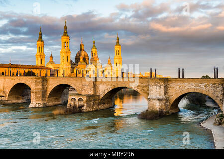 Cathedral of Our Lady of the Pillar and stone bridge at sunrise. Zaragoza, Aragon, Spain, Europe - Stock Image