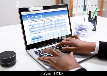 Close-up Of A Businesswoman's Hand Filling Online Survey Form On Laptop In Office - Stock Image