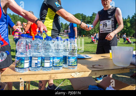 Plastic bottled water being handed out to runners at the finish on the 2018 Sherwood Pines 10k. - Stock Image