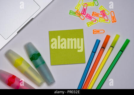 Sticky notes with markers, colored pens, paper clips laying on a table, Back to school, School and office supplies. - Stock Image